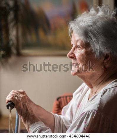 Portrait of  old woman sitting with a cane at home - stock photo