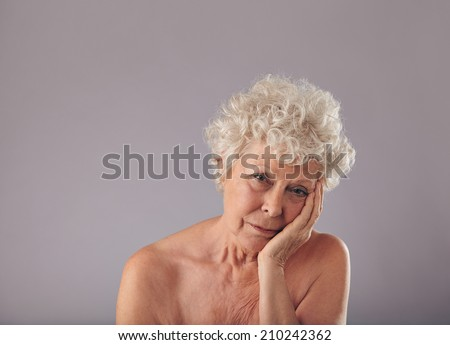 Portrait of old woman with a tired look on her face against grey background. Upset senior woman holding her face in hand and looking at camera. - stock photo