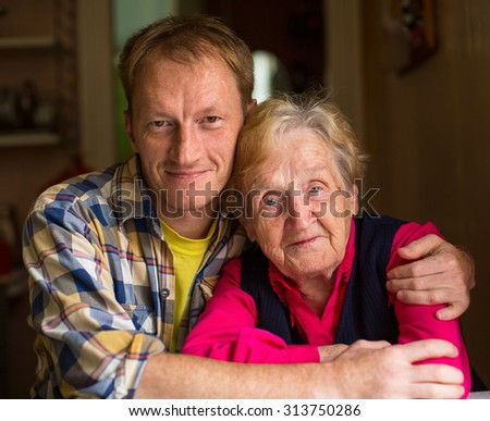 Portrait of old woman with an adult grandson. - stock photo