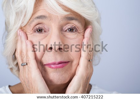 Portrait of older pretty woman with a few wrinkles. Touching her face with hands - stock photo