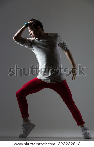 Portrait of one attractive fit young man dancing, working out wearing casual outfit. Modern style cool dancer guy standing in shadow. Full length photo image on studio gray background - stock photo
