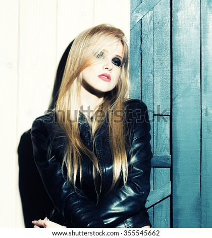 Portrait of one attractive sensual sexy young serious passionate blonde woman with long hair in leather black jacket in studio on wooden wall background, square picture - stock photo