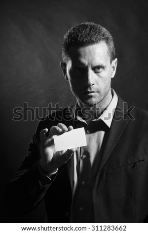 Portrait of one attractive sexy unshaven young man in jacket and shirt holding business card in hand looking forward standing on studio background black and white copyspace, vertical picture - stock photo