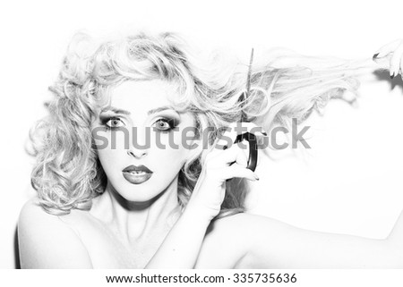 Portrait of one beautiful sensual sexy young retro blonde woman with curly hair and bright makeup looking forward holding scissors in studio black and white, horizontal picture