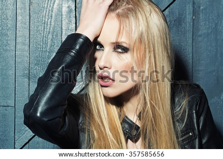Portrait of one beautiful sensual sexy young serious passionate blonde woman touching head and long hair with hand in leather black jacket in studio on wooden wall background, horizontal picture - stock photo