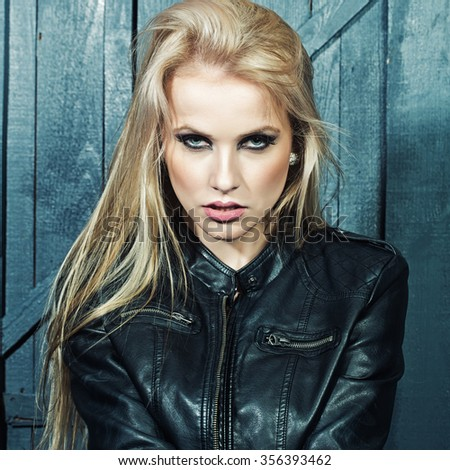 Portrait of one beautiful sensual sexy young serious passionate blonde woman with long hair in leather black jacket in studio on wooden wall background, square picture