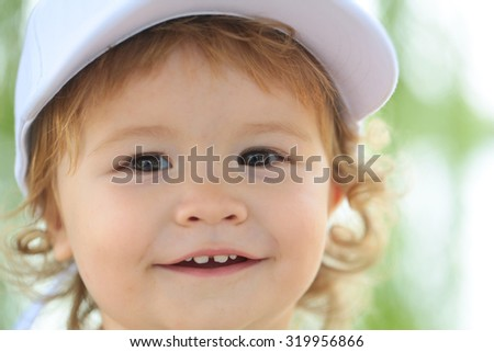 Portrait of one little happy smiling male child swith blond curly hair in white cap on green natural blur background closeup, horizontal picture - stock photo