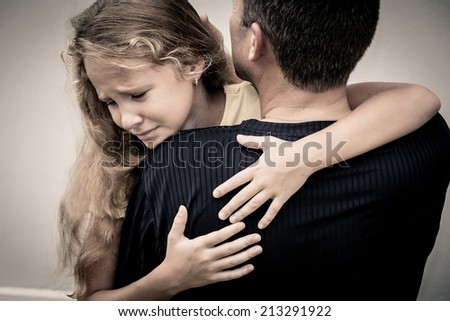 portrait of one sad daughter hugging his father - stock photo