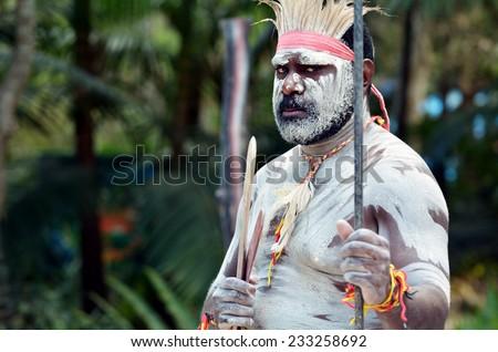 Portrait of one Yugambeh Aboriginal warrior man preform Aboriginal culture martial art during Aboriginal cultural show in Queensland, Australia. - stock photo