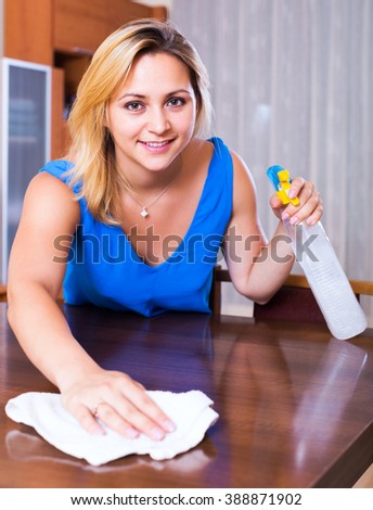 Portrait of ordinary girl in blue blouse dusting furniture indoors - stock photo