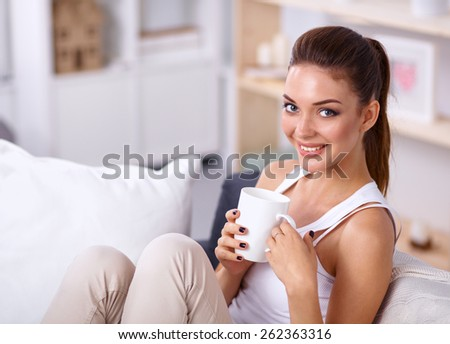 Portrait of oung beautiful woman with a cup on sofa at home - stock photo