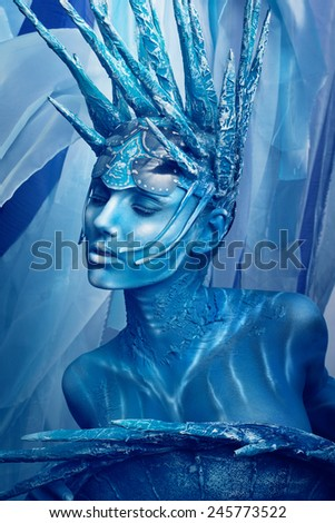 Portrait of painted woman in original head wear on blue background
