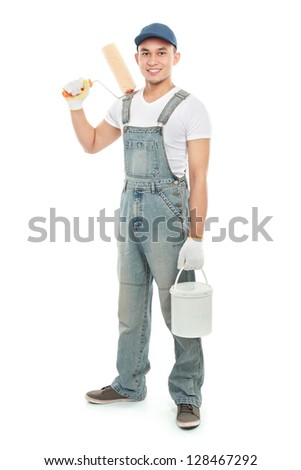 portrait of Painter with paintbrush ready to paint the wall - stock photo