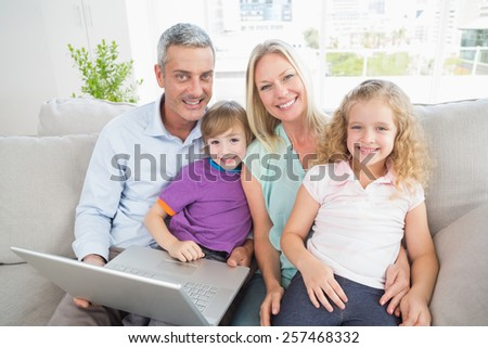 Portrait of parents and children with laptop sitting on sofa at home - stock photo