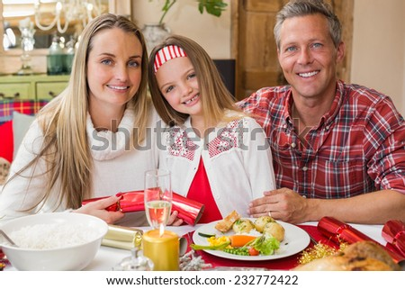 Portrait of parents and daughter together at christmas time at home in the living room - stock photo