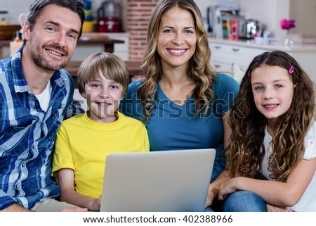 Portrait of parents and kids sitting on sofa and using a laptop at home - stock photo