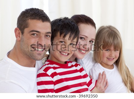 Portrait of parents, daughter and son in living-room sitting on sofa together