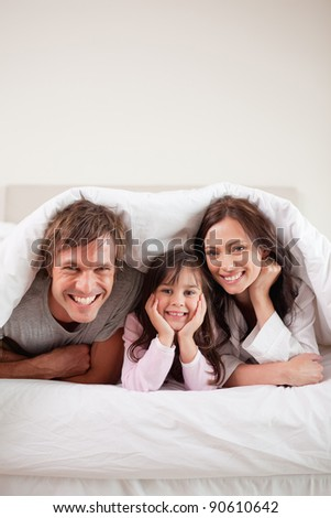 Portrait of parents lying under a duvet with their daughter in their bedroom - stock photo