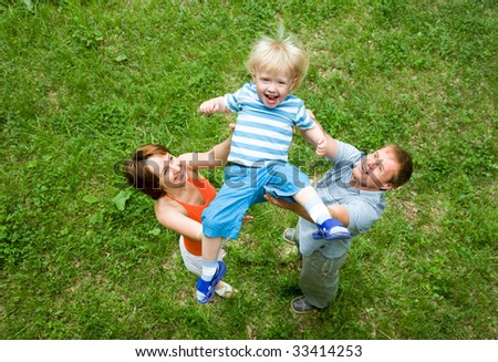 Portrait of parents throwing up son outdoor - stock photo