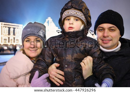 Portrait of parents with a small son during the New Year festivities in the evening