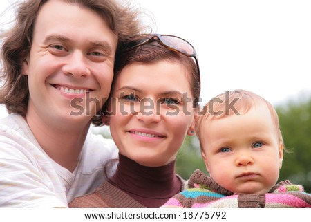 Portrait of parents with baby on nature
