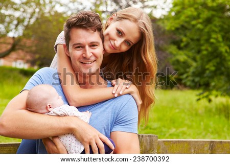 Portrait Of Parents With Baby On Walk In Countryside - stock photo
