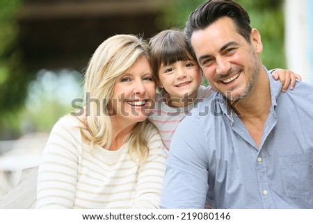 Portrait of parents with daughter sitting outside