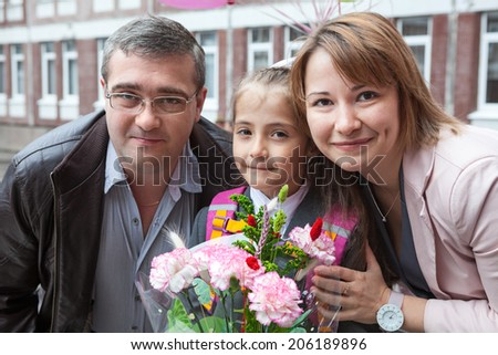 Portrait of parents with schoolgirl before going back to school - stock photo