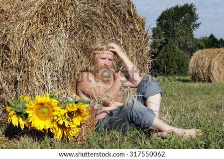 portrait of peasant in a field, thinking about life in summer day - stock photo