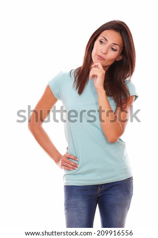 Portrait of pensive adult 30s woman on blue t-shirt and blue jeans looking at people while standing on white background - copyspace - stock photo