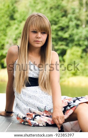 Portrait of pensive blond girl in white dress sitting on the steps of the sun against the background of a summer day - stock photo