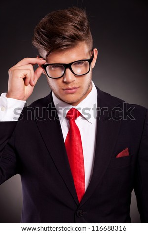 Portrait of pensive business man holding his eyeglasses on dark background