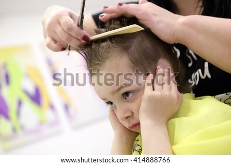 Portrait of pensive child at the barbershop - stock photo