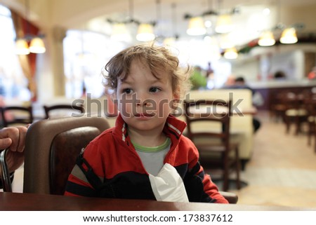 Portrait of pensive child at the table in a cafe