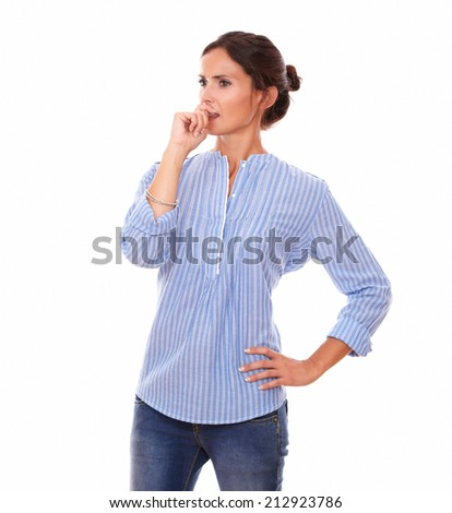 Portrait of pensive lady on blue blouse looking to her right while standing on isolated white background - copyspace - stock photo