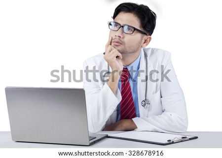 Portrait of pensive male doctor looking upward with notebook computer and clipboard on the tablet
