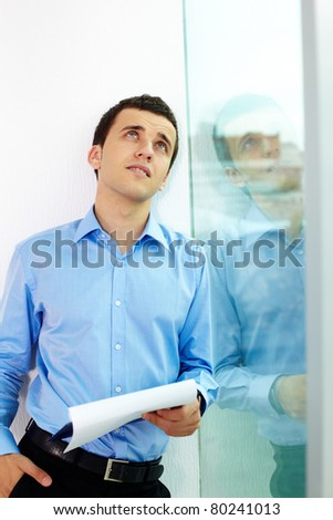 Portrait of pensive man with document looking upwards in office - stock photo