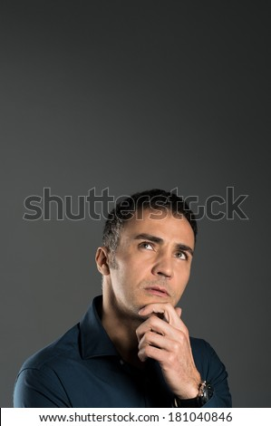Portrait Of Pensive Mature Man With Hand On Chin On Grey Background - stock photo