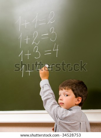 Portrait of pensive schoolchild standing at blackboard and doing sums - stock photo