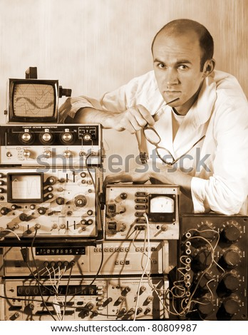 Portrait of pensive scientist at vintage technological laboratory. Sepia toned - stock photo