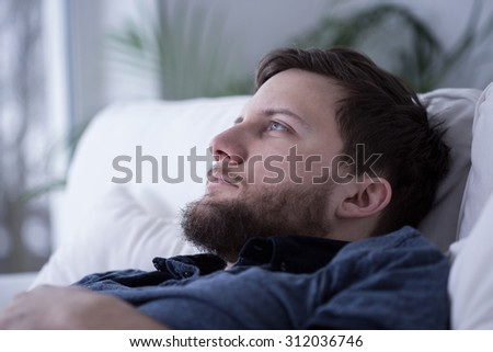 Portrait of pensive tired male unable to fall asleep