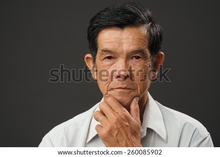 Portrait of pensive Vietnamese senior man - stock photo