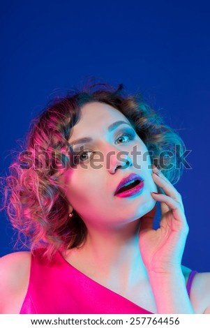 Portrait of pensive woman in studio on a blue background - stock photo