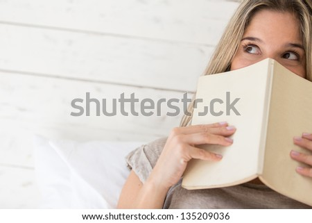 Portrait of pensive woman reading a book - stock photo