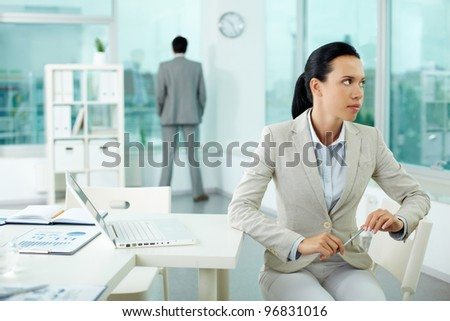 Portrait of pensive young businesswoman at her workplace looking aside - stock photo