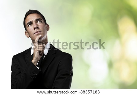 portrait of pensive young man with suit against a plants background