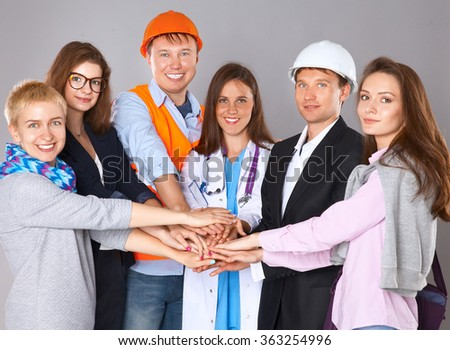 Portrait of people with various occupations putting their hands on top of each other - stock photo
