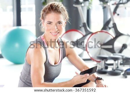 Portrait of personal trainer woman sitting at gym after fitness workout and  using her smartphone.