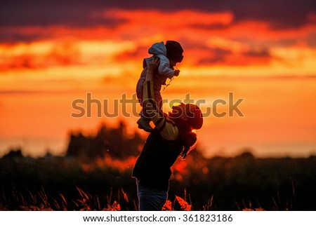 Portrait of picture of happy mother with baby on sunset background - stock photo