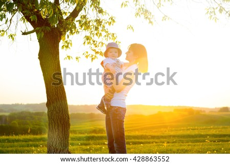 Portrait of picture of happy mother with baby on sunset background. Happy mother and son at sunset sunlight.